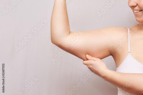 Obraz na plátne Young woman pinch fat arm