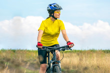Beautiful Girl In Yellow Riding A Bike In Nature. Sports And Recreation. Hobbies And Health.