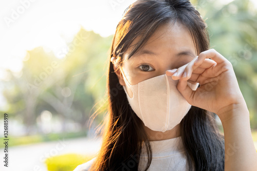 Fotografie, Tablou Asian child girl wearing protective mask,people rubbing the eyes due to air poll