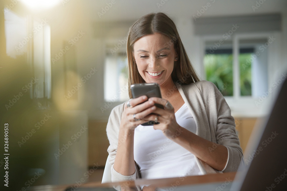 Fototapeta Cheerful woman at home using smartphone