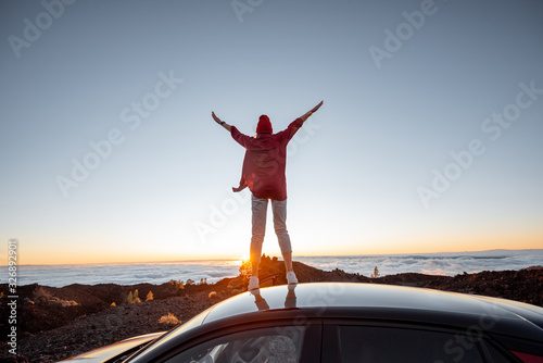 Obraz Woman enjoying rocky landscapes above the clouds on a sunset, standing on the car highly in the mountains. Carefree lifestyle and travel concept - fototapety do salonu