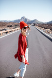 Lifestyle portrait of a young woman stylishly dressed in red walking on the beautiful road in the midst of volcanic valley on a sunny day. Carefree lifestyle and travel concept
