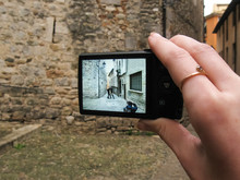 A Hand Holding A Camera With A Picture On The Screen: An Outdoor Photographer Taking A Picture Of A Young Couple Standing In The Ancient Street