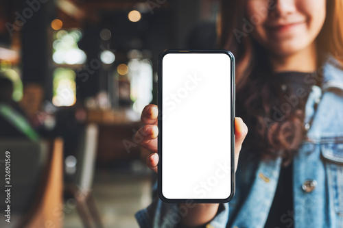 Fotografía Mockup image of a woman holding and showing black mobile phone with blank white