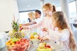 Kinder holen sich frisches Obst am Büffet