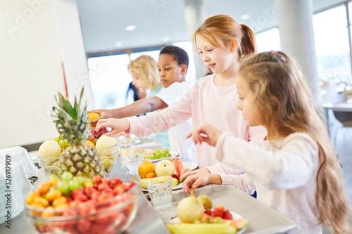 Kinder holen sich frisches Obst am Büffet - 326917909
