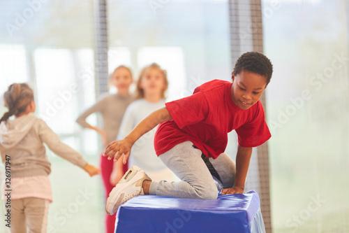 Tela Kinder turnen an einem Sprungkasten