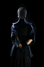 Kendo Fighter In Full Uniform On A Black Background Silhouette. In A Mask For Fencing.