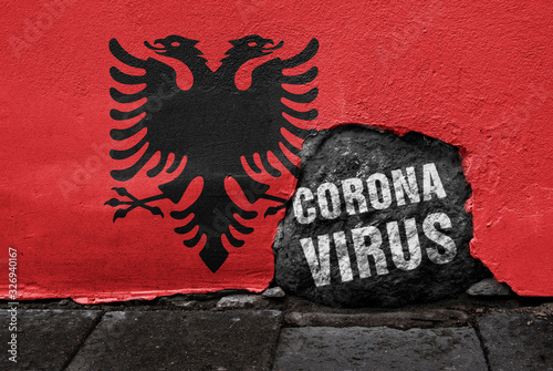 Photo Flag of Albania on the wall with cracked stone with text Coronavirus on it