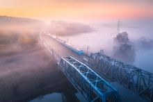 Aerial View Of Speed Train On Railroad Bridge And River In Fog At Sunrise In Fall. Autumn Landscape With Foggy Fields, Mist, Water, Trees, Railway Station, Orange Sky With Gold Sunlight. Top View