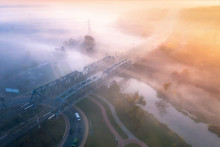 Aerial View Of Beautiful Railroad Bridge And River In Fog At Sunrise In Fall. Autumn Landscape With Foggy Meadows, Mist Over The Water, Trees, Railway Station, Orange Sky With Gold Sunlight. Top View
