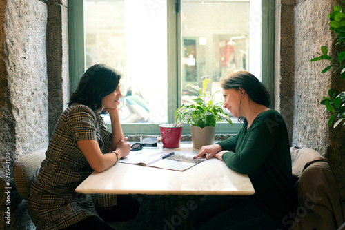 Two friends sitting in a coffee shop by the window having fun while they talk Wallpaper Mural