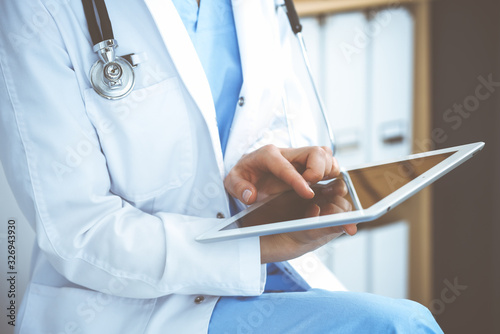 Woman doctor using white tablet computer while sitting at chair in hospital, clo Fototapet