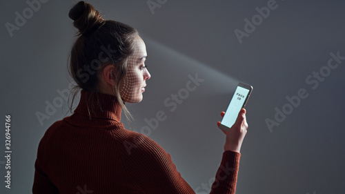 Fotografía Female scans face using facial recognition system on smartphone for biometric identification