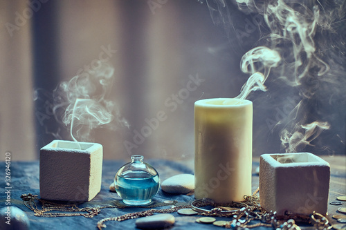 Fototapeta Group of magic smoke candles and a bottle elixir potion for a divination occult