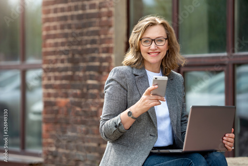 Fototapeta Portrait of a happy mature business woman using her mobile phone and laptop, outdoors, near the office