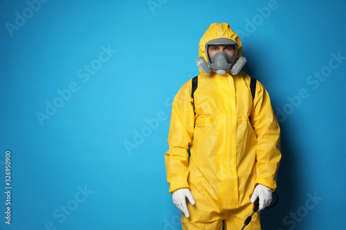 Fotomural Man wearing protective suit with insecticide sprayer on blue background, space for text