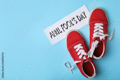 Photo Sport shoes tied together and note with phrase APRIL FOOL'S DAY on light blue background, flat lay
