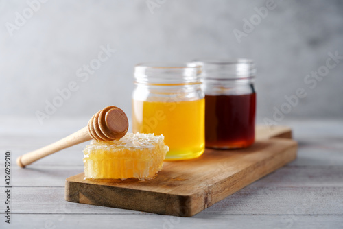 Obraz Fresh honey and honeycombs on wooden cutting board. Light floral and dark honey in glass jars - fototapety do salonu