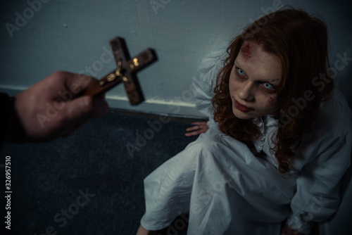 Wallpaper Mural exorcist holding cross in front of obsessed girl