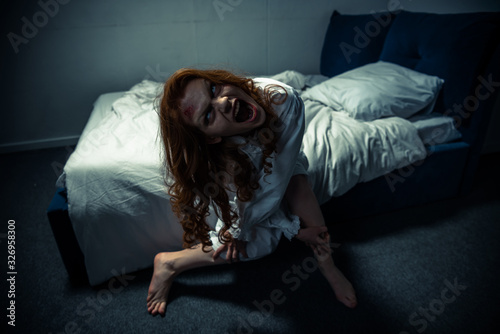 Photo demonic woman in nightgown screaming in bedroom