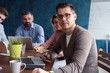 Happy to be a part of great team. Cheerful young handsome man looking at camera with smile while sitting at the office table on business meeting with his coworkers.