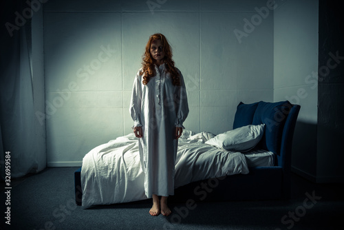 Fotomural creepy demoniacal girl in nightgown standing in bedroom
