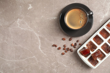 Ice cubes, cup of coffee and beans on grey table, flat lay. Space for text