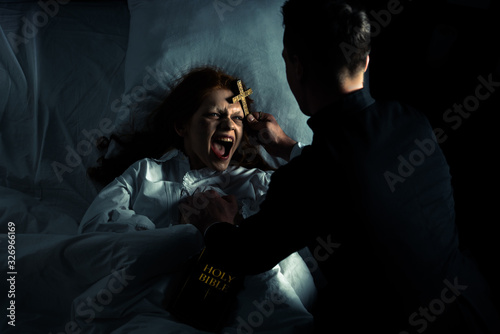 Fotografia exorcist with bible and cross standing over demoniacal yelling girl in bed