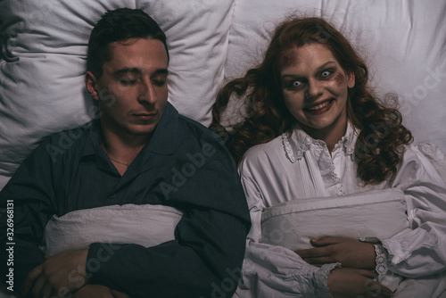 Cuadros en Lienzo top view of creepy smiling female demon lying in bed with sleeping man