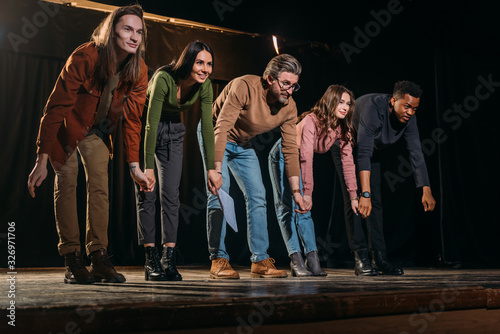 Fototapeta happy actors and actresses bowing on stage obraz