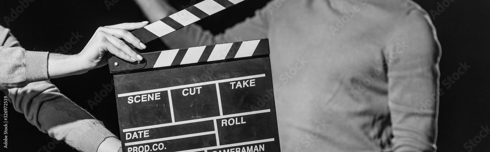 Fototapeta panoramic shot of actor with clapboard in front, isolated on black, black and white