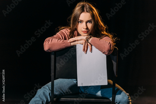 Canvas attractive young actress with scenario sitting on chair on stage in theatre
