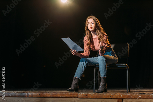 Photo attractive young actress with scenario performing role on stage in theatre