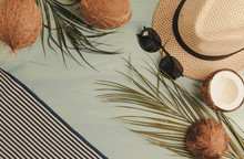 Summer Composition Or Layout. Tropical Palm Leaves, Hat, Glasses, Beach Towel, Coconut On A Background Of Sea Greens. The Concept Of The Summer Season And Heat. Flat Lay, Top View, Copy Space