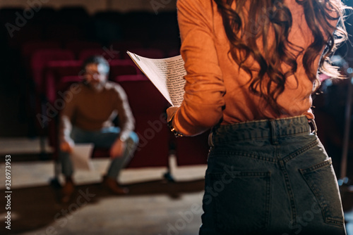 Photo selective focus of theater director and actress with screenplay on stage