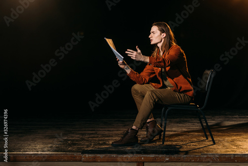 Canvas Print handsome actor with scenario playing on stage during rehearse in theatre