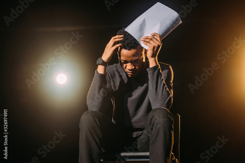 stressed african american actor holding scenario on stage during rehearse Poster Mural XXL