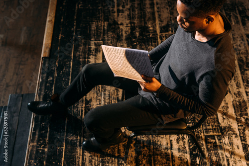 Obraz handsome african american actor holding scenario on stage during rehearse - fototapety do salonu