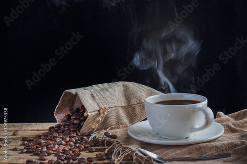 Fototapety, obrazy: White hot coffee cups and roasted coffee beans on a wooden table have a black backdrop.