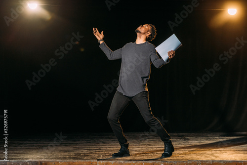 Obraz african american actor holding scenario and standing on stage during rehearse in theatre - fototapety do salonu