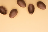Top view of chocolate eggs on beige background