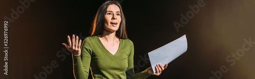 Photo panoramic shot of attractive young actress reading scenario on black