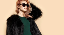 Portrait Of Modish Beautiful Woman. Charming Model Wearing Black Furry Coat, Green Blouse And Dark Sunglasses. Attractive Blonde Touching Hair With Hand. Isolated On Beige