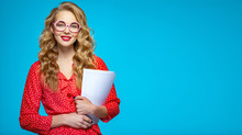 Businesswoman In A Casual Clothes Holds Papers Posing At Studio. Woman Secretary In A Red Shirt Over Blue Background Holding Documents.  Female Student In A Pink Glasses Holding Documents.