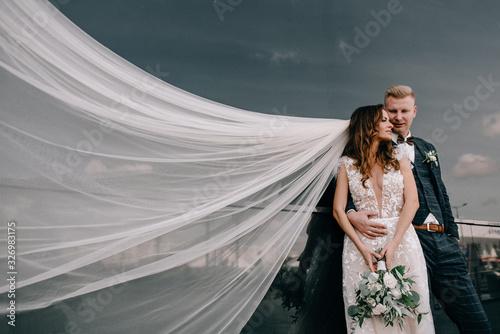 Fotografia, Obraz Happy bride and groom posing in city