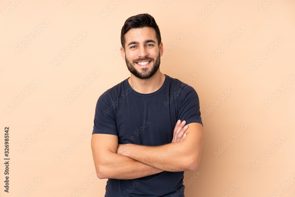 Fototapeta Caucasian handsome man isolated on beige background keeping the arms crossed in frontal position