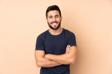 Caucasian handsome man isolated on beige background keeping the arms crossed in frontal position