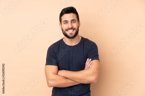Fototapeta Caucasian handsome man isolated on beige background keeping the arms crossed in