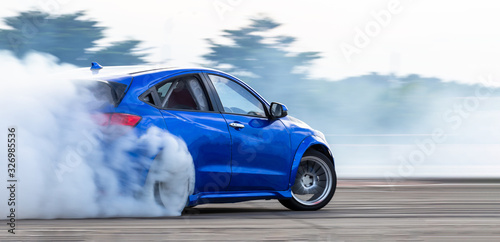 Stampa su Tela Car drifting, Blurred  image diffusion race drift car with lots of smoke from burning tires on speed track